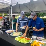 Making plates of food at the Collins Vision 15th Anniversary Cookout