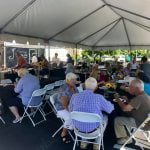 A large crowd eating lunch under a tent at the Collins Vision Cookout