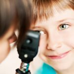 Ophthalmologist examines the eye of a child.